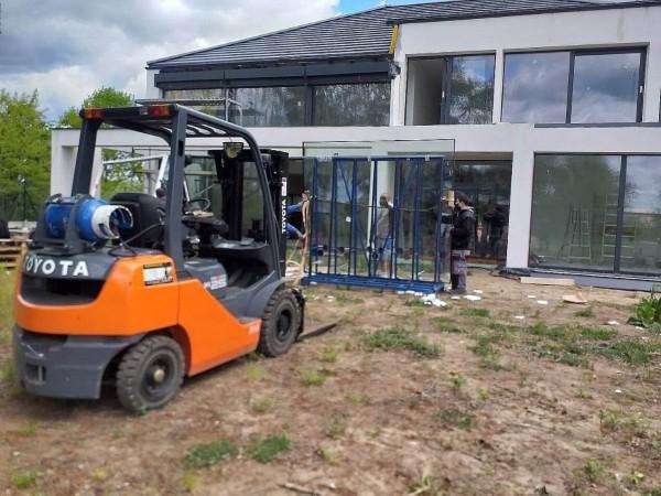 pomarańczowy wózek widłowy przy budowie domu